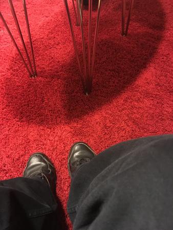 Röd väntrumsmatta och mina fötter och ben i svart