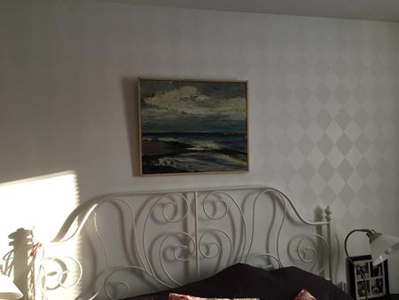 En olja med havsmotiv ovanför sängen.