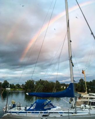Regnbågen bakom båtarna i Motala hamn